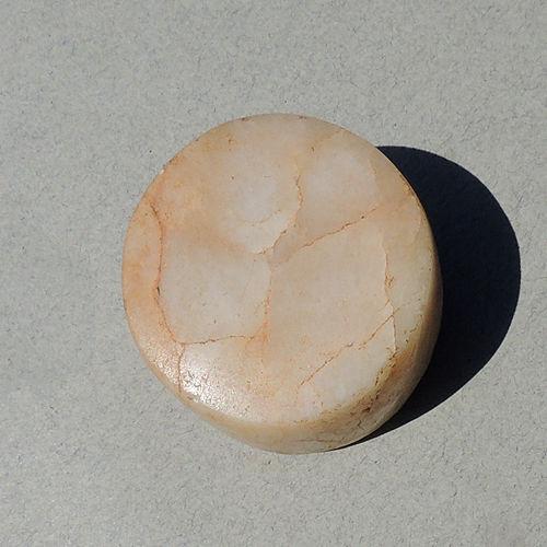 A quartz lip or ear plug, found in Mali. Neolithic.