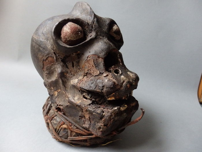 A  nkisi  from Cross River area of Cameroon/Nigeria. This head was sold at auction in Germany. The skin was claimed to be antelope stretched over wood, with real teeth. Mid-20th century.