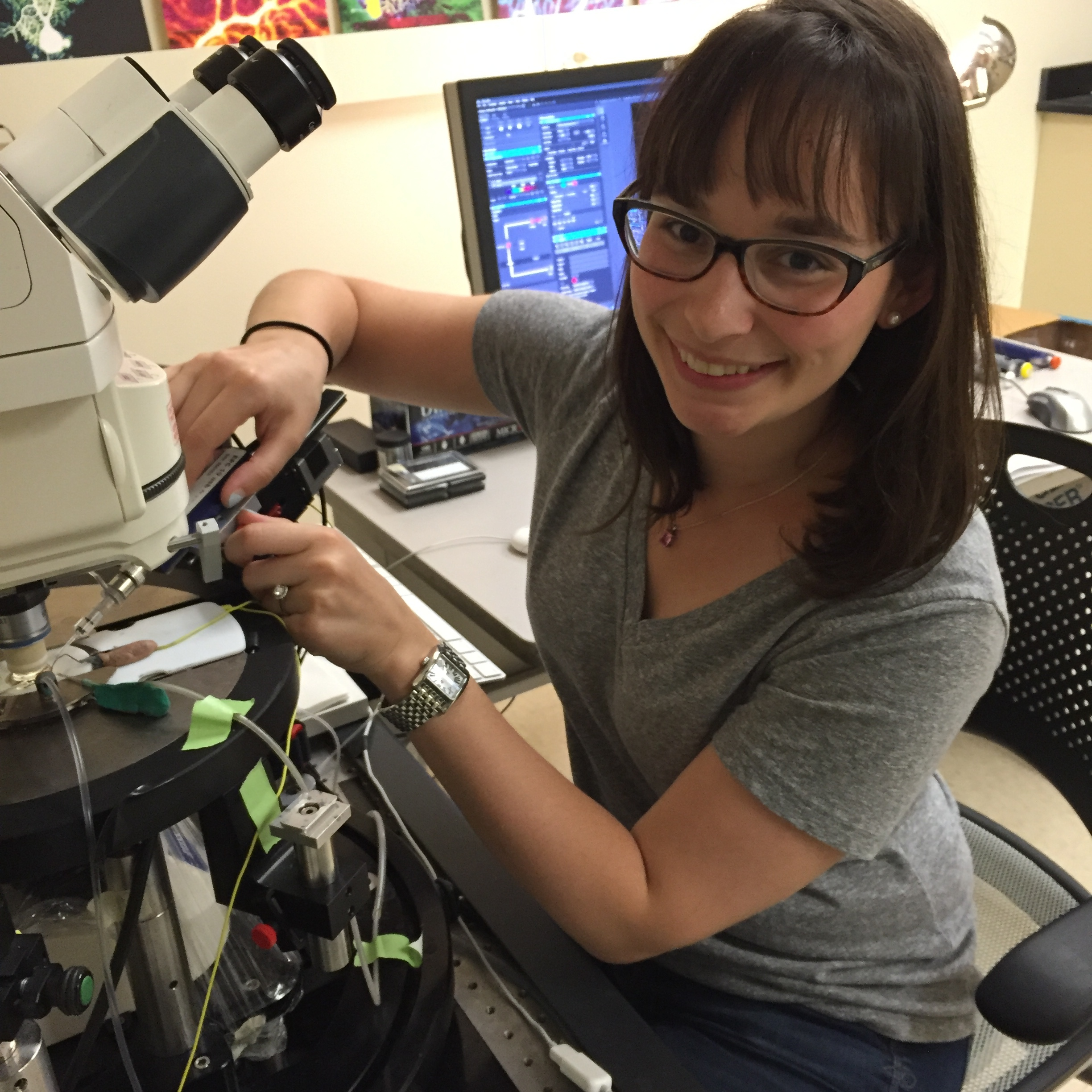 Dana, performing experiments at the microscope in the Hansel Lab at The University of Chicago