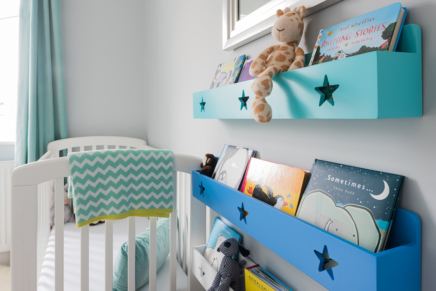 View of bookshelf and cot in peacock coloured unisex nursery