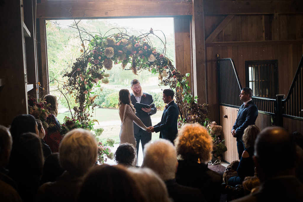 Wedding ceremony in a horse barn - Pearl Weddings & Events