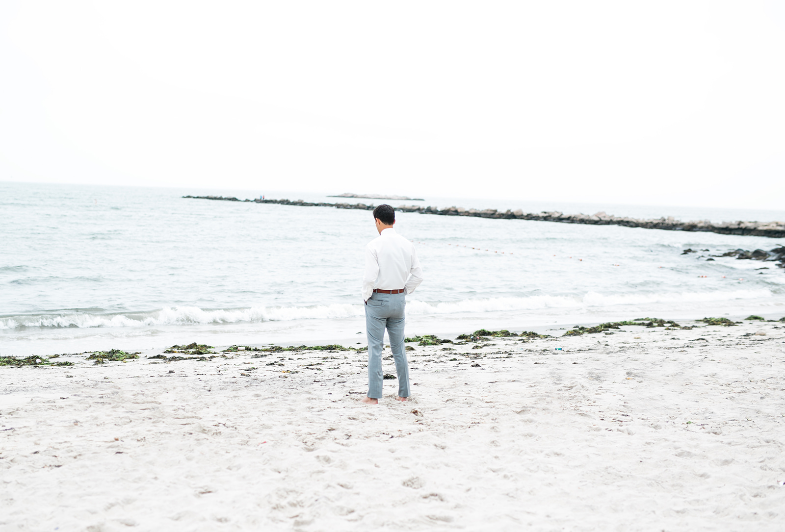 Groom awaits his bride for the first look next to the ocean - Pearl Weddings & Events