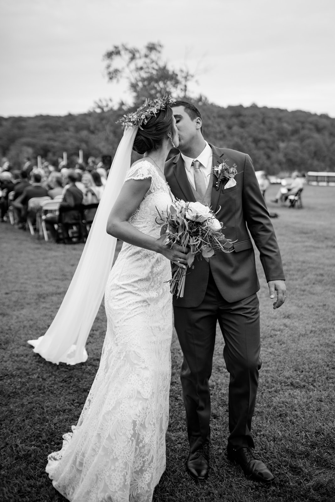 Couples kiss after the ceremony - Floral crown with a veil in a black and white photo - Pearl Weddings & Events