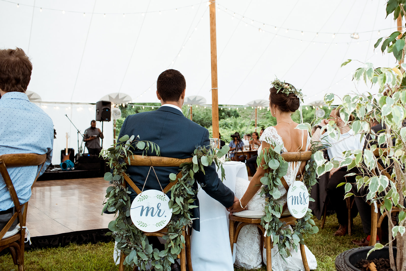 Bride and groom holding hands at their sweetheart table with their chairs hanging Mr & Mrs. sign and greenery! - Pearl Weddings & Events