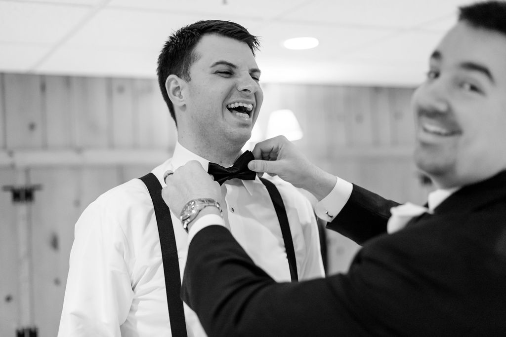 The best man and groom getting ready for the ceremony with their bow ties and suspenders - Pearl Weddings & Events