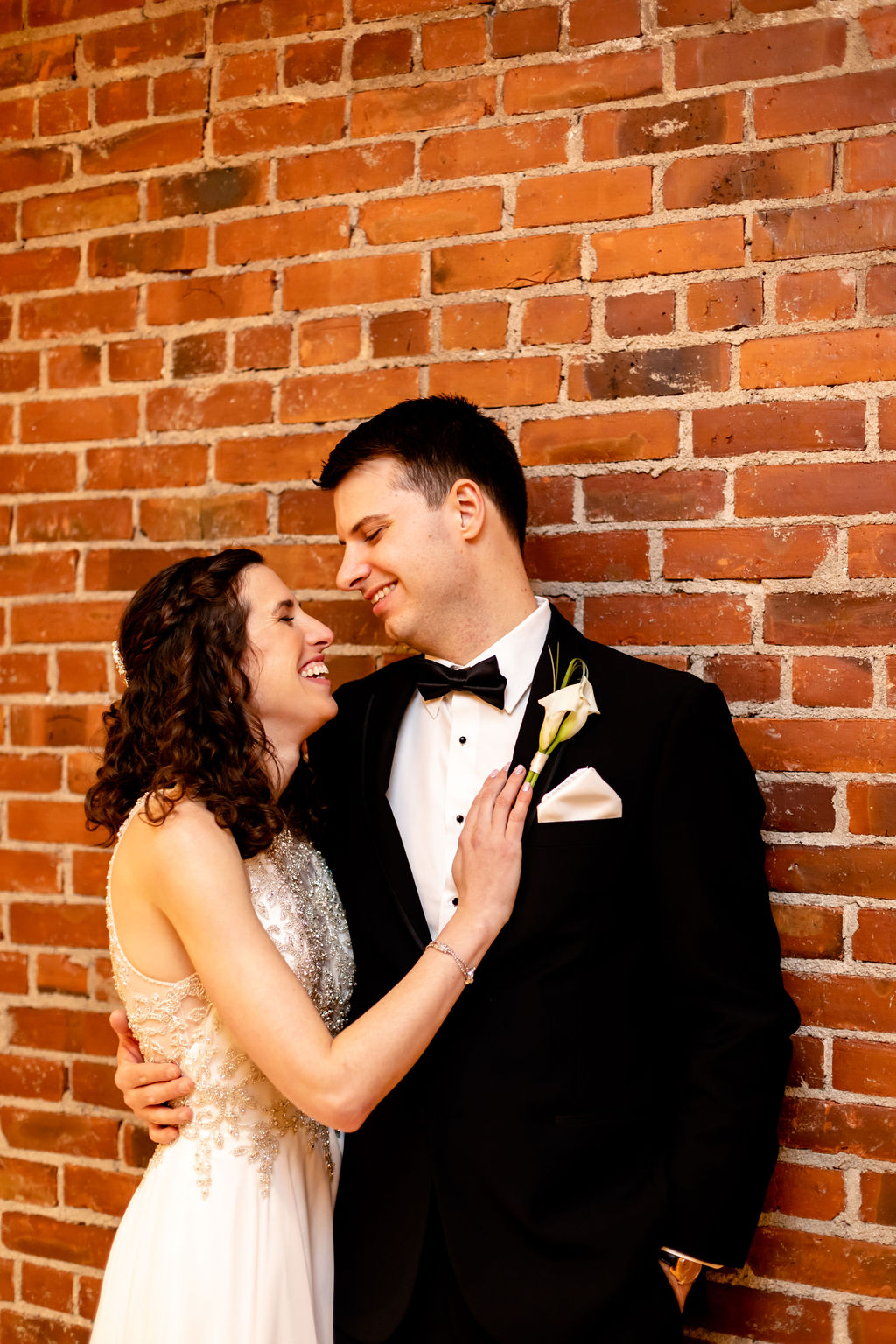Bride and groom against a brick wall - Pearl weddings & Events