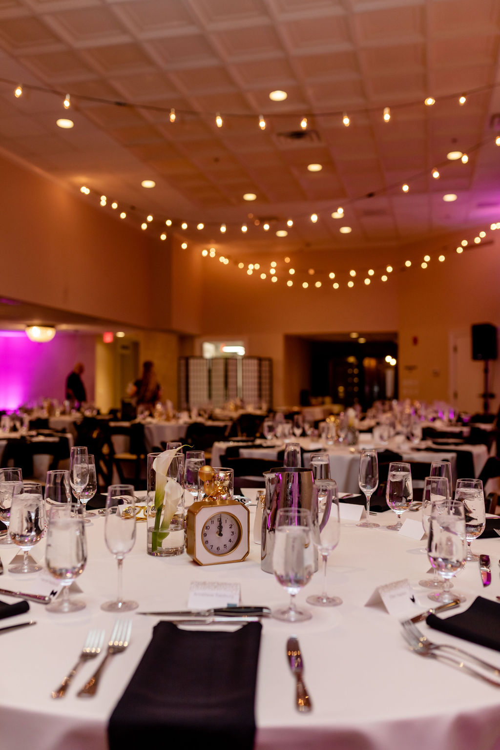 New Years Eve wedding table details with black napkins, ivory table linens, clocks, calla lilies and ornaments with twinkly lights - Pearl Weddings & Events