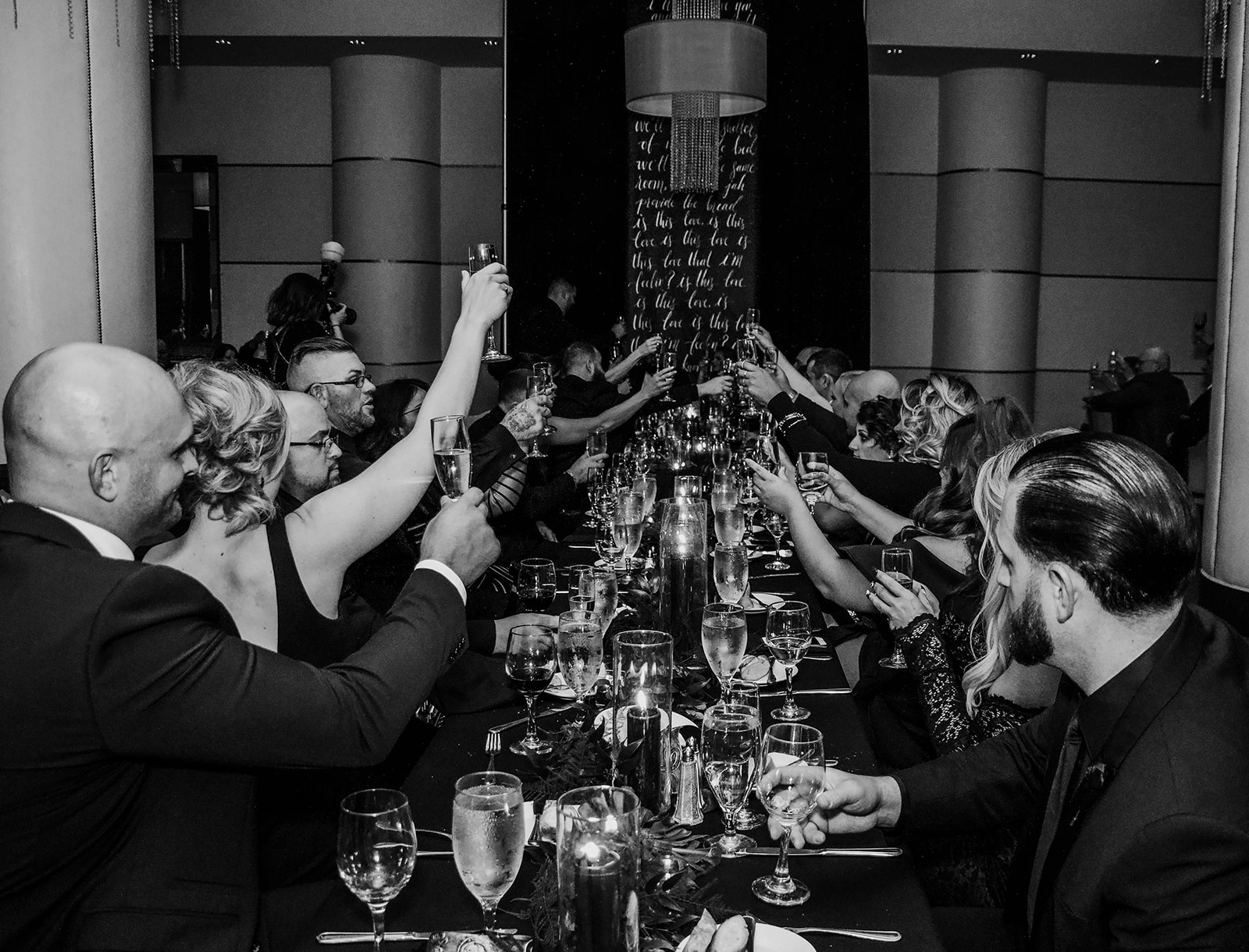 cheers in the reception space with the head table being the entire bridal party and a black backdrop for the sweetheart tables - Pearl Weddings & Events