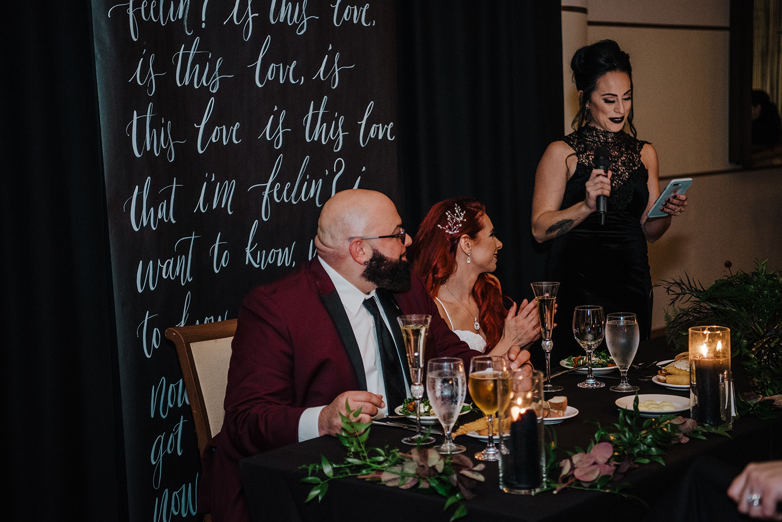black details at the sweetheart table with the back drop that has the lyrics to the couples first dance song - Pearl Weddings & Events