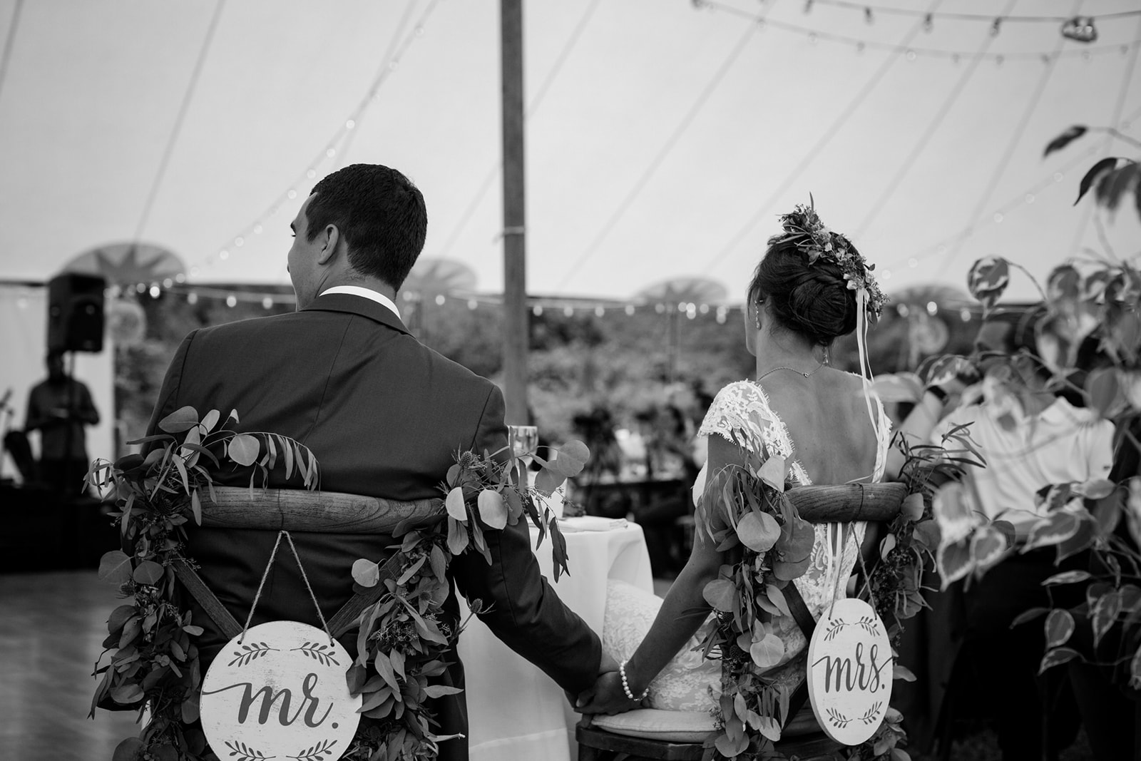Bride and groom holding hands at their reception sweetheart table with cross back wooden chairs, greenery and mr. and mrs. signs hanging on the back of their chairs - Pearl Weddings & Events