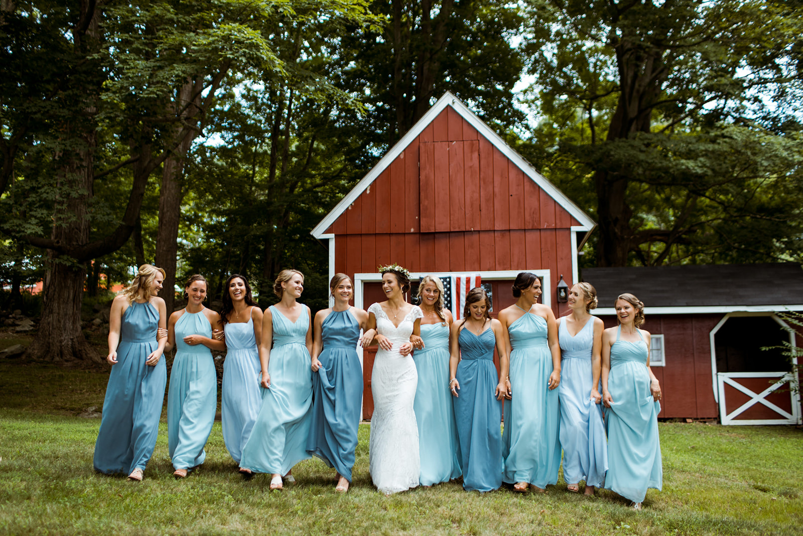 different shades of blue bridesmaid dresses. Bride with a flower crown. Red barn at Tiny Tiffany's farm. Chester, Connecticut outdoor tented wedding. - Pearl Weddings & Events