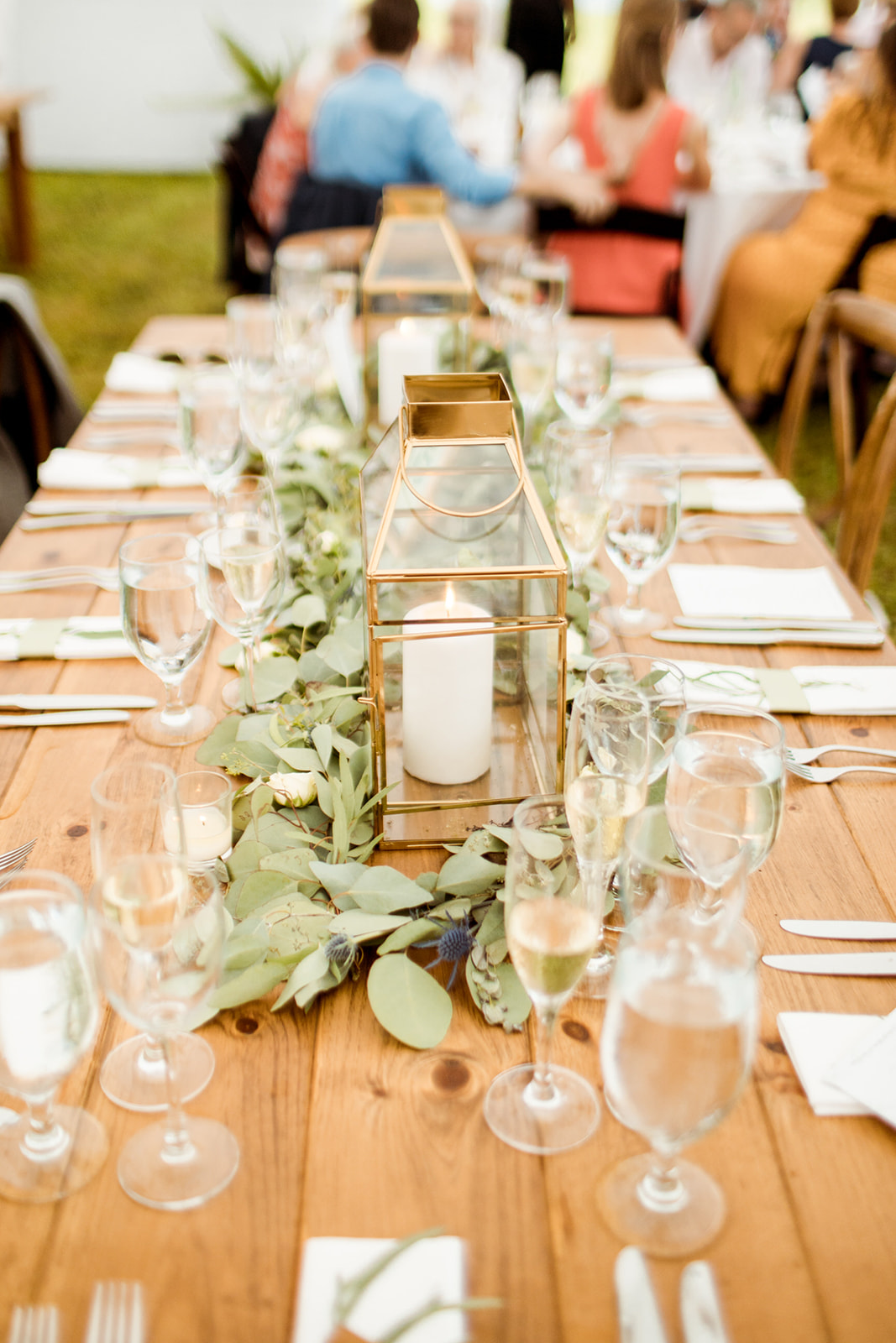 Greenery on farm tables with vintage white napkins and gold candle holders - Pearl Weddings & Events