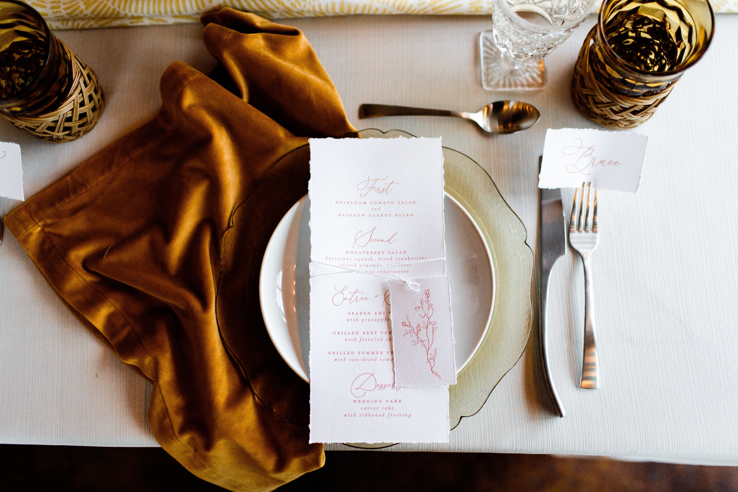 Yellow chargers with white plates, white menus with pink lettering and gold vintage glassware - Pearl Weddings & Events