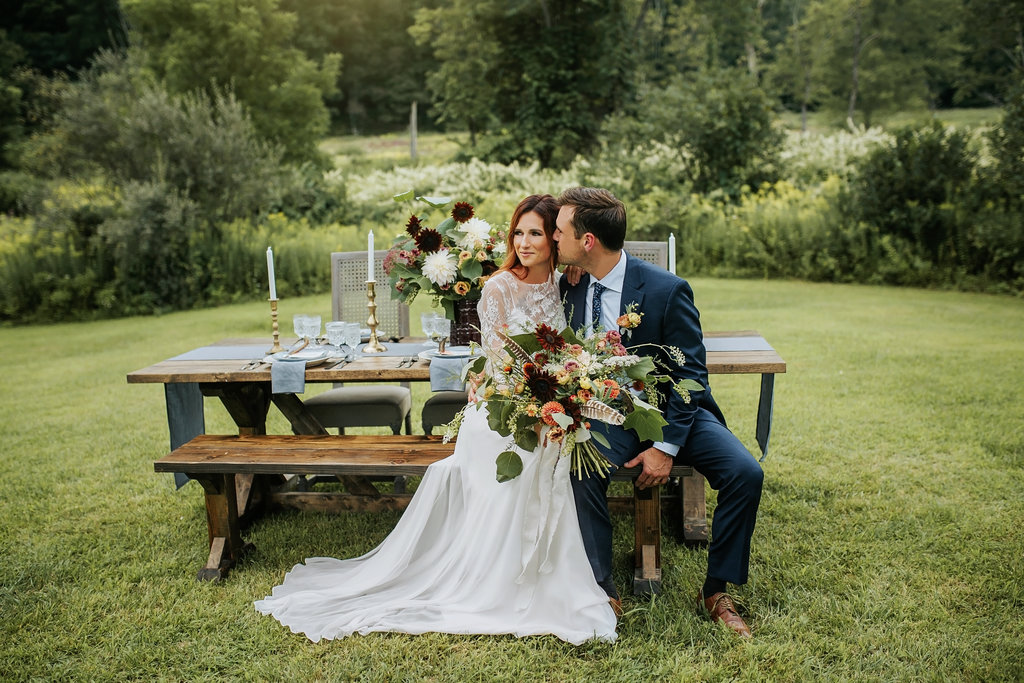 Bride and Groom at their farm table, bench and wicker chairs,  with blues and oranges hues at Great Hollow Nature Preserve -