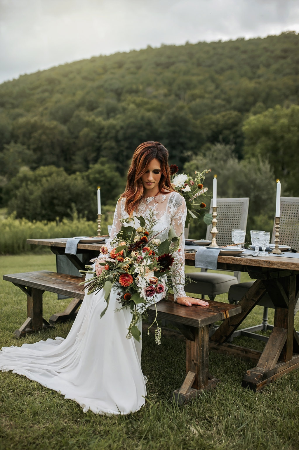 Bride in a two piece wedding dress with a floral bouquet that has feathers in it! -Pearl Weddings & Events