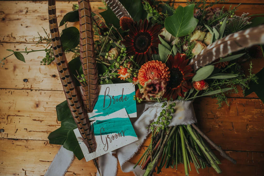 Moody bouquet with feathers and plantable name cards! - Pearl Weddings & Events