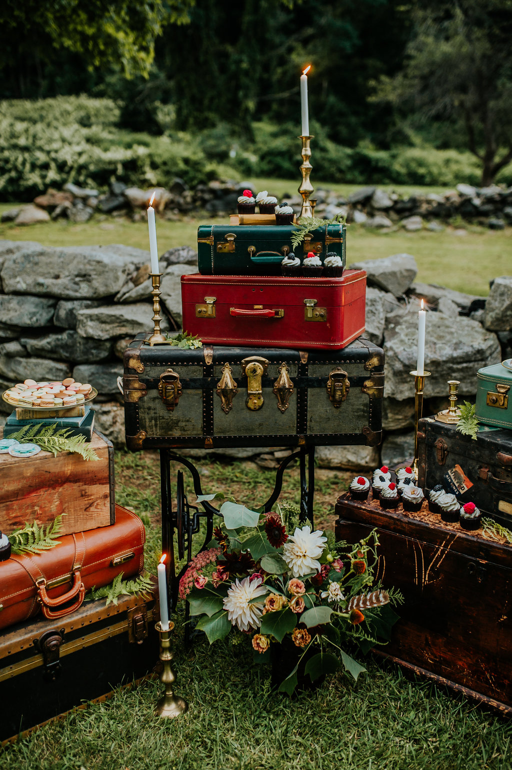 Dessert display with vintage suitcases, taper candles and floral bouquets - Pearl Weddings & Events