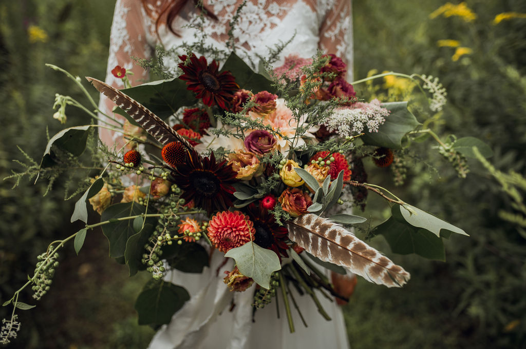 Gorgeous bouquet with deep moody tones and feather! - Pearl Weddings & Events