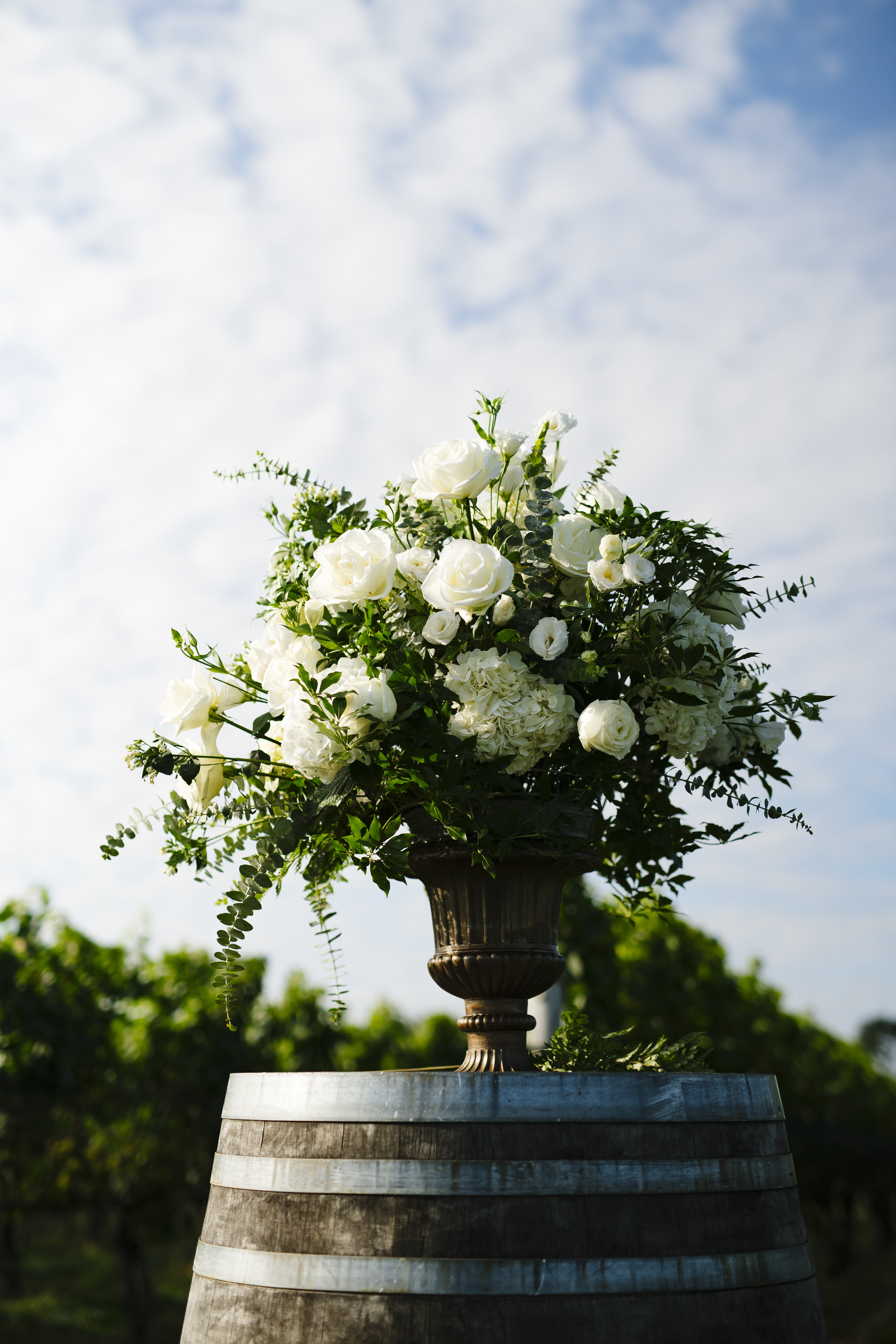 Blue, white and green florals on a wine barrel for the ceremony at Jonathan Edwards Winery in Connecticut - Pearl Weddings & Events