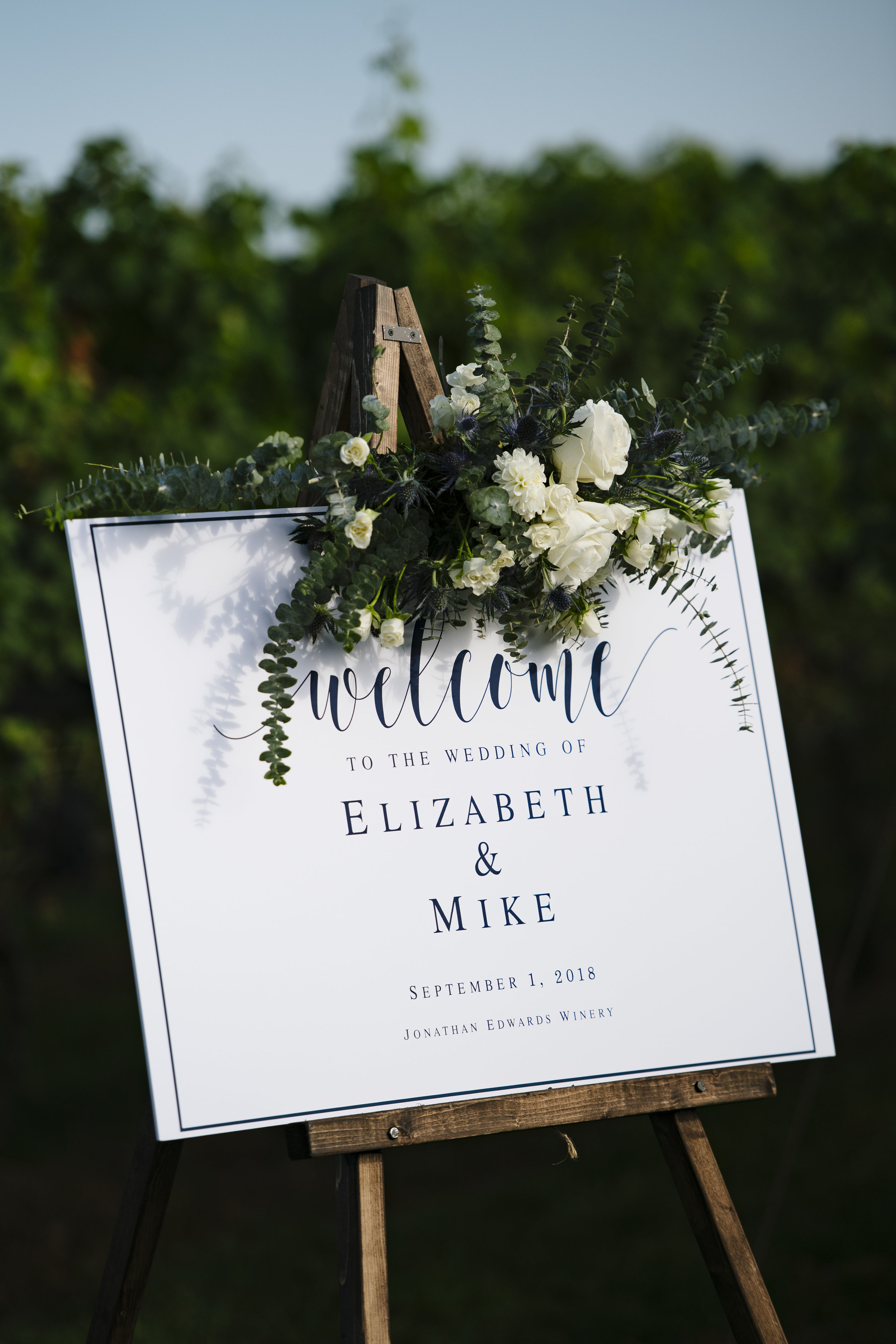 White and navy blue welcome sign on an easel with florals at the top at Jonathan Edward Winery in Connecticut - Pearl Weddings & Events
