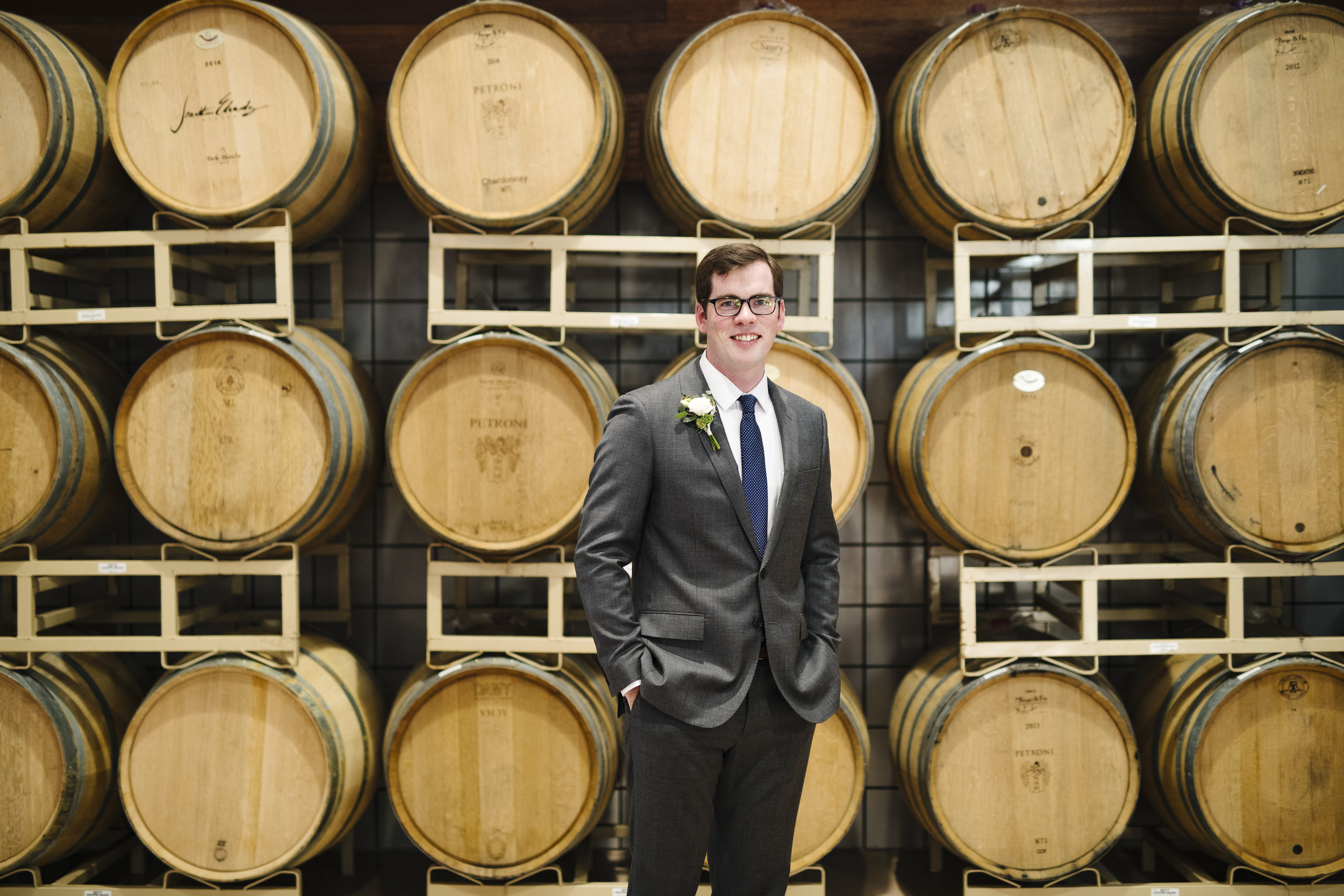 Groom photos in front of wine barrels at jonathan edwards winery - Pearl Weddings & Events