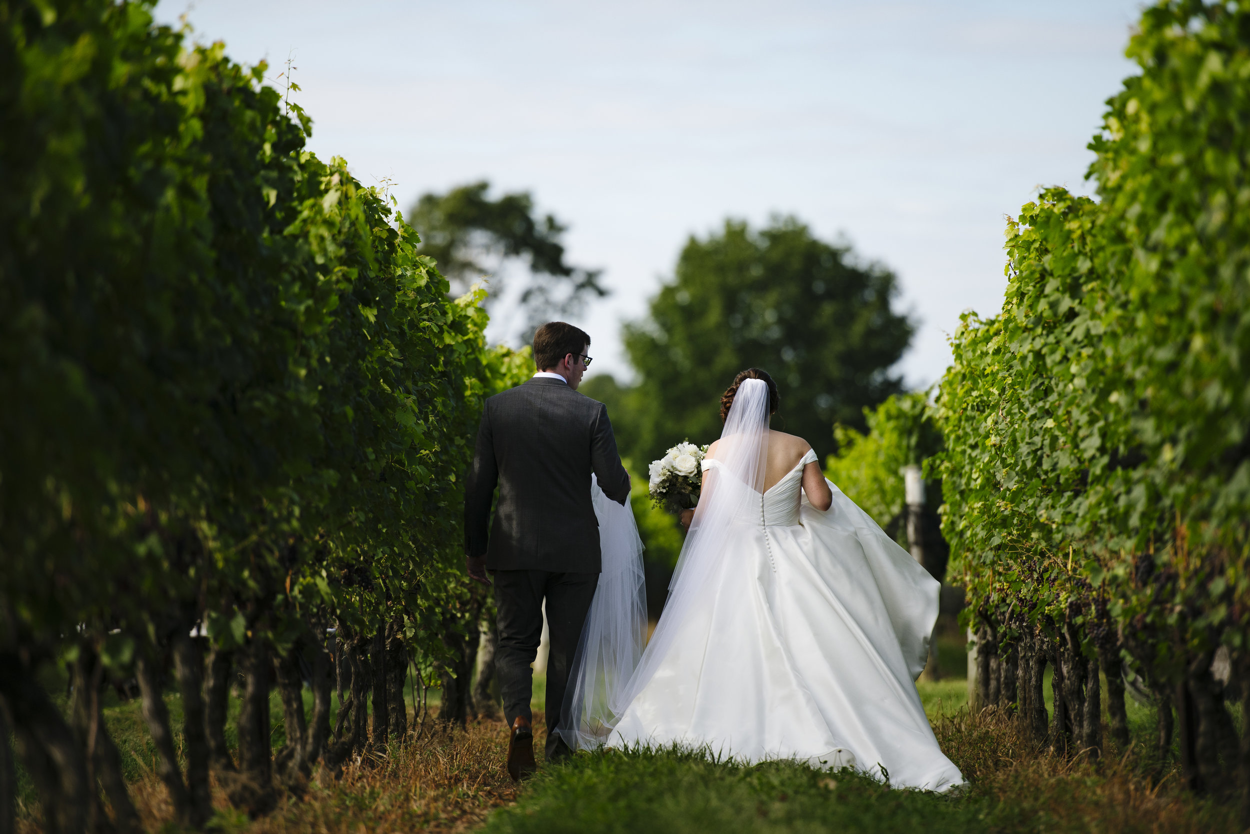 Bride and groom first look in the vineyard at Jonathan Edwards Winery in Connecticut - Pearl Weddings & Events