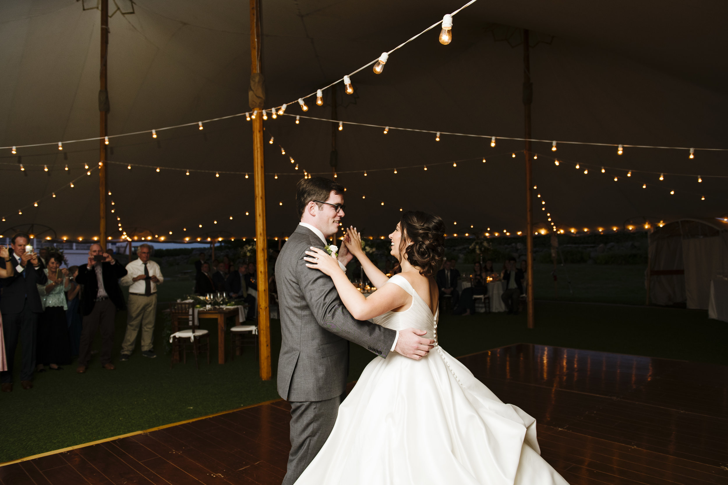 First dance on dance floor under a tent with cafe strung lighting at Jonathan Edwards Winery in Connecticut - Pearl Weddings & Events
