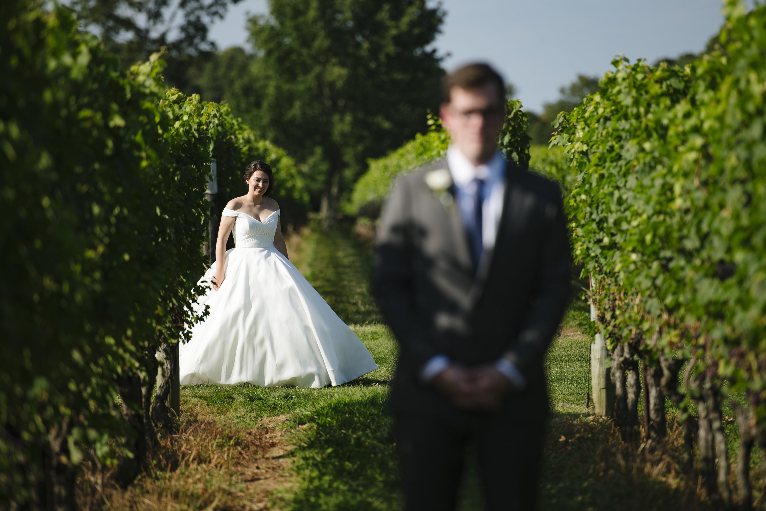 the bride and groom first look in the vineyard at Jonathan Edwards Winery. - Pearl Weddings & Events