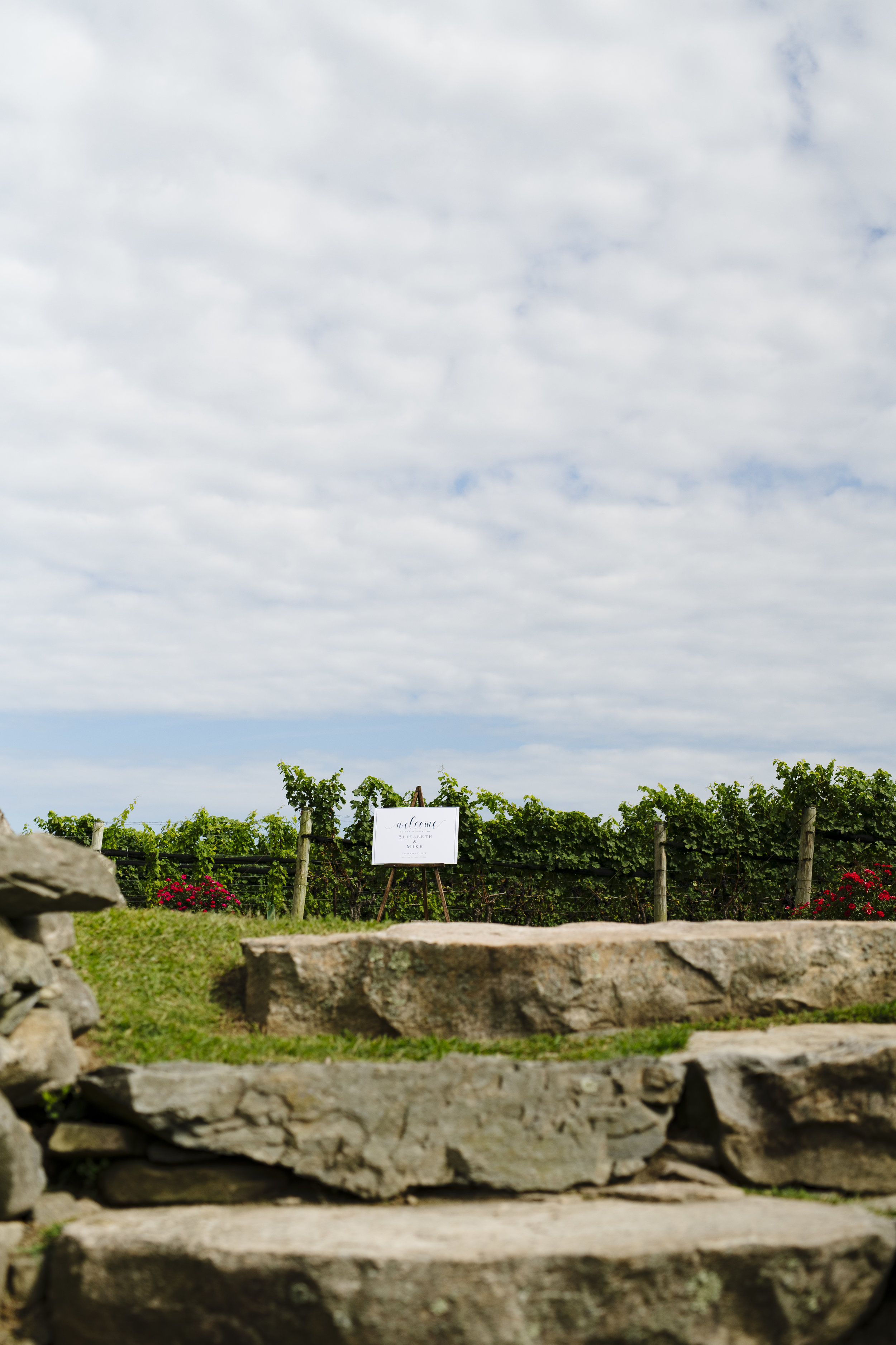 Jonathan Edwards Winery wedding. Ceremony set up with welcome sign in the vineyard of the Connecticut wine trail - Pearl Weddings & Events