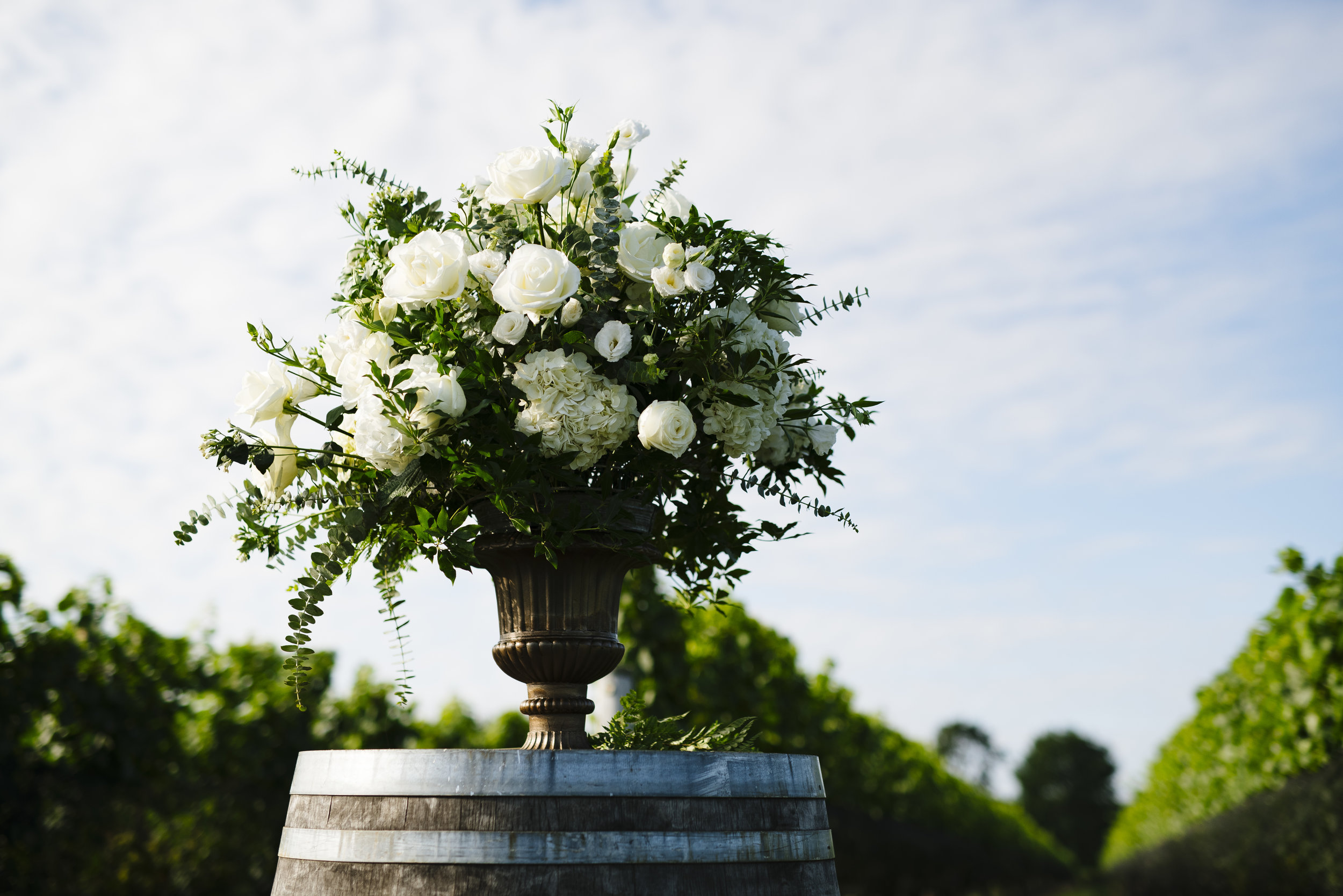 White and green ceremony floral arrangements on a rustic wine barrel at Jonathan Edwards Winery - Pearl Weddings & Events