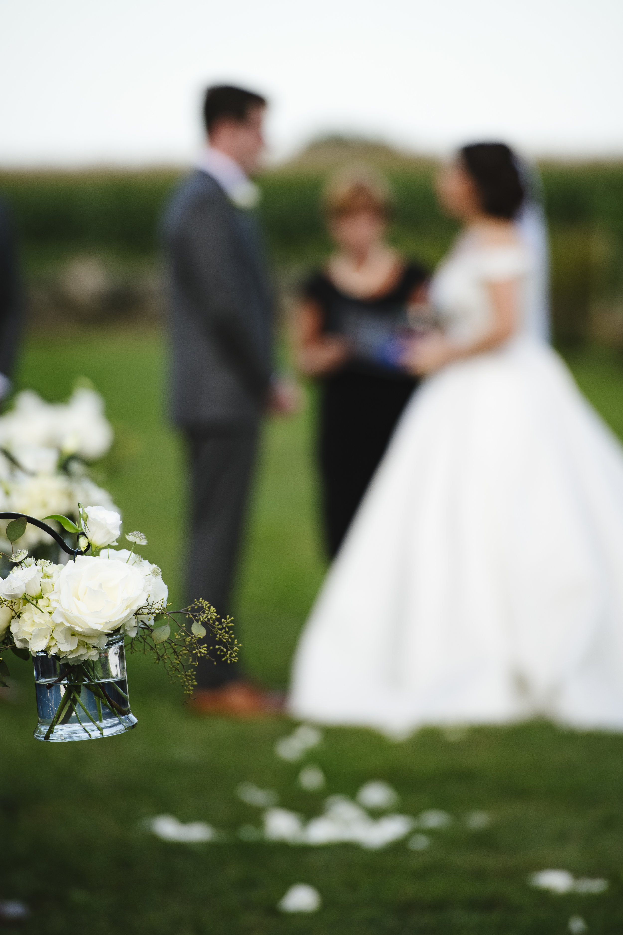Mason jars filled with white roses on hooks down the aisle at a Jonathan Edwards Winery wedding ceremony in Connecticut - Pearl Weddings & Events