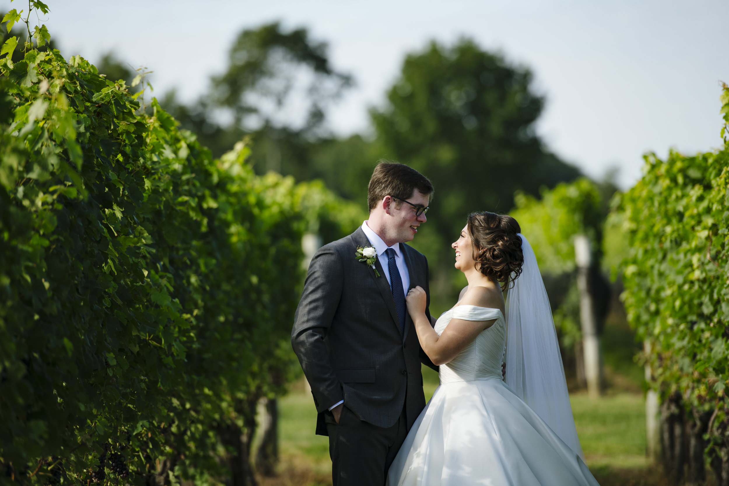 bride and groom in the vineyard for their first look at Jonathan Edwards Winery - Pearl Weddings & Events