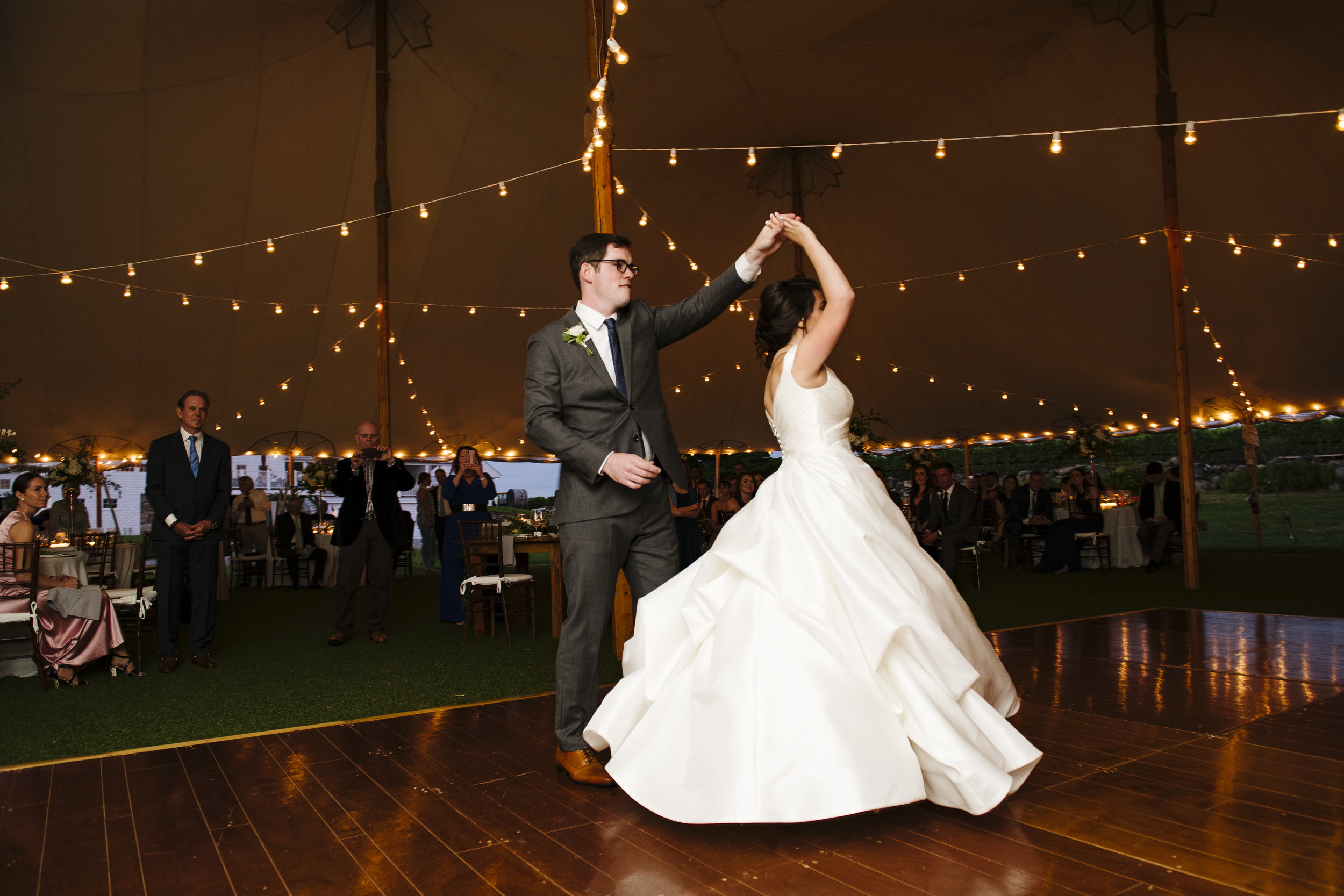 First dance under cafe lighting in a sperry tent at Jonathan Edwards Winery in Connecticut - Pearl Weddings & Events