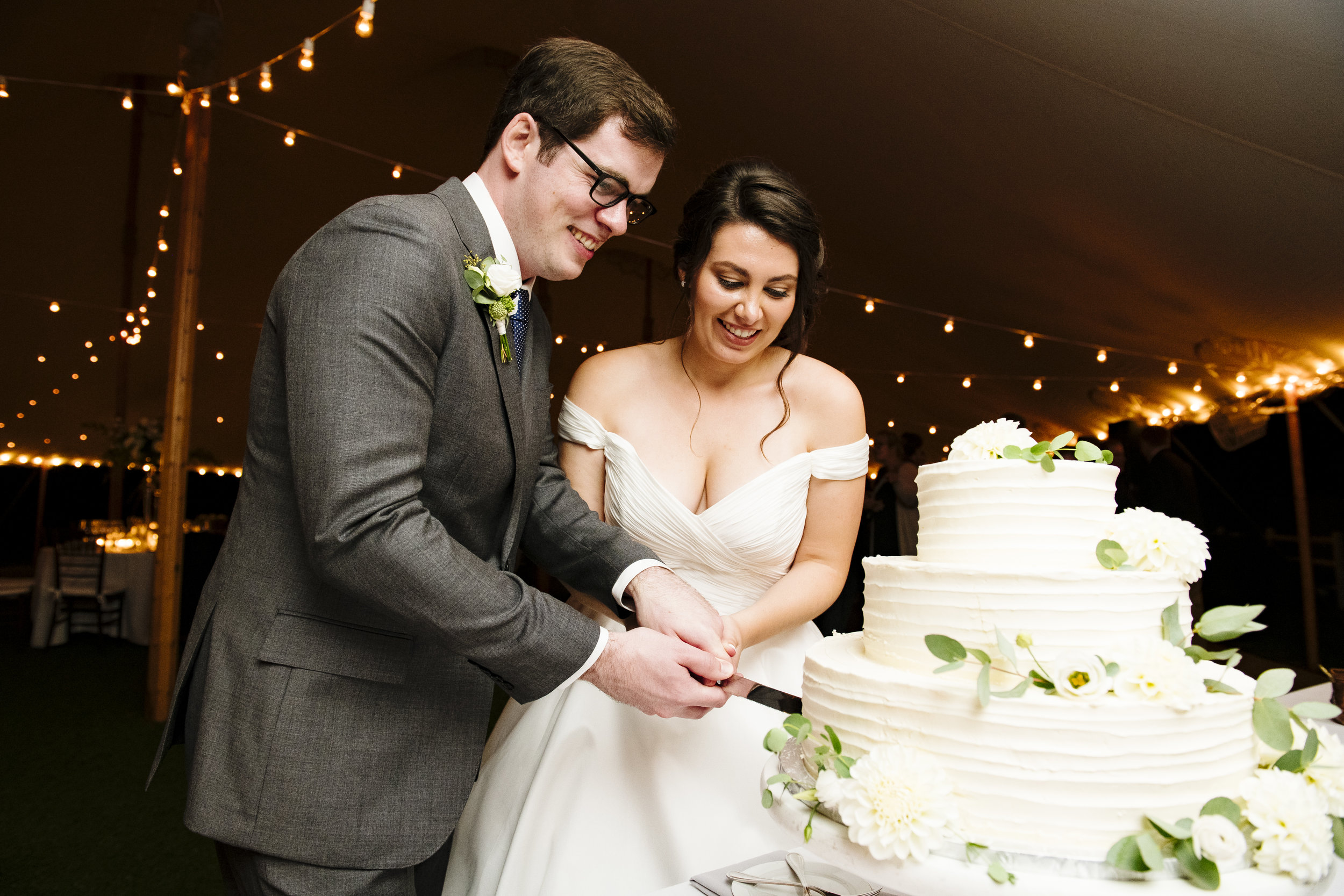 Cutting the cake made by A Thyme To Cook at Jonathan Edwards Winery in Connecticut - Pearl Weddings & Events