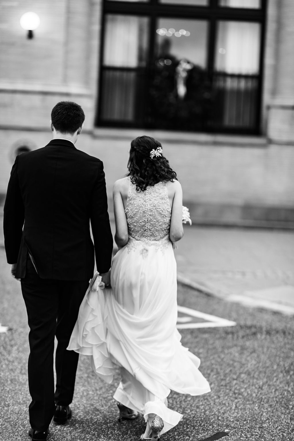 When the groom carries the brides dress so she doesn't trip - Pearl Weddings & Events