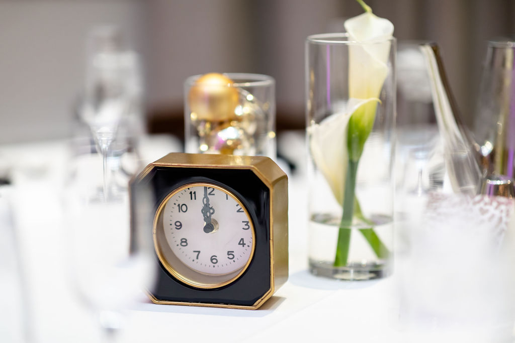 Clocks at midnight, calla lilies on the table and ornament in tall hurricane glasses - Pearl Weddings & Events