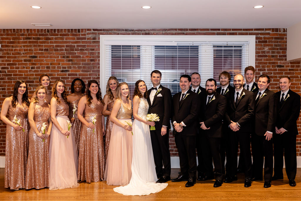 Bride and groom and their wedding party. Groomsmen are in all black and the bridesmaids are in blush pink . - Pearl Weddings & Events