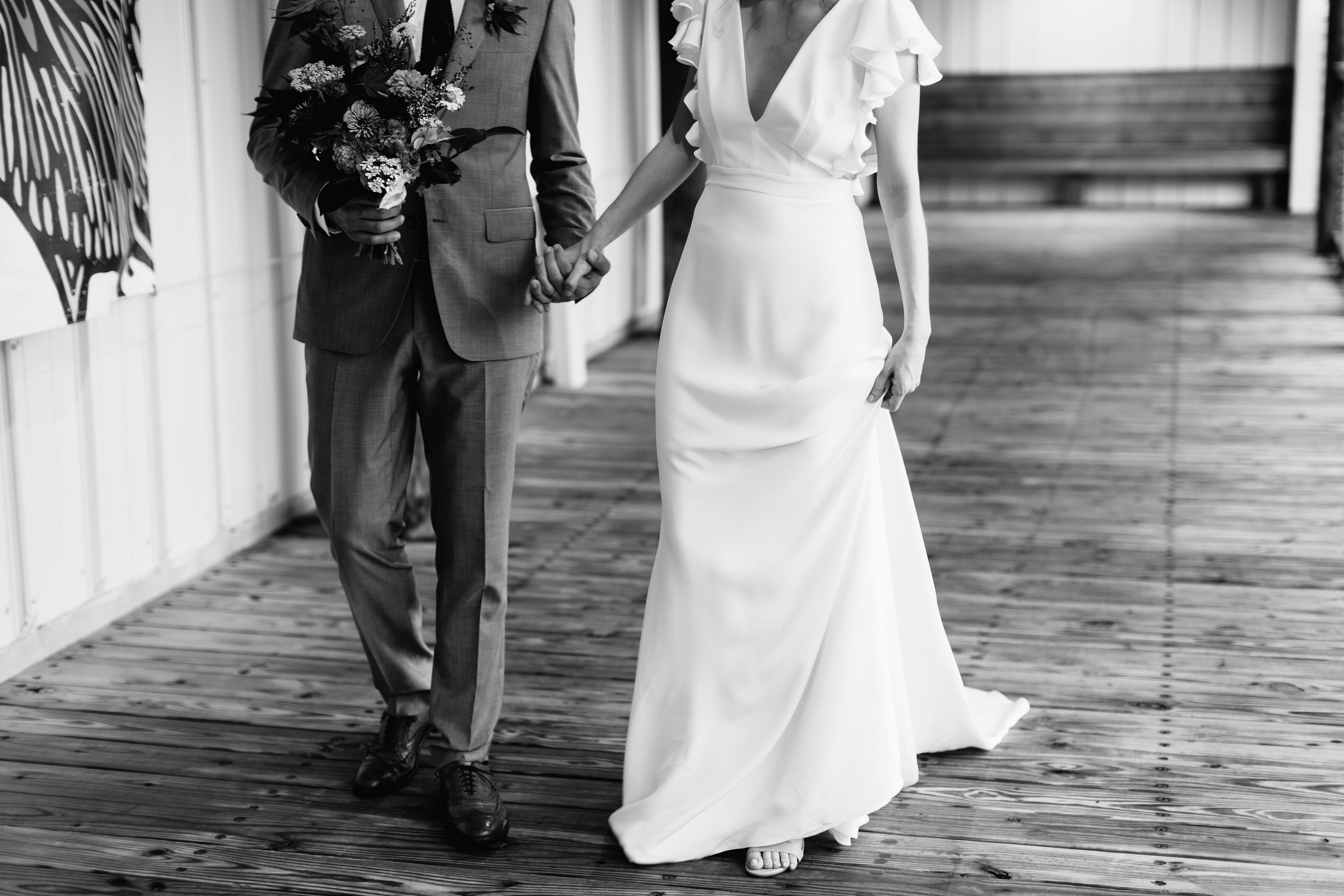 Groom holding the bride bouquet. Bride dressed in Alexander Grecco from Everthine Bridal. - Pearl Weddings & Events