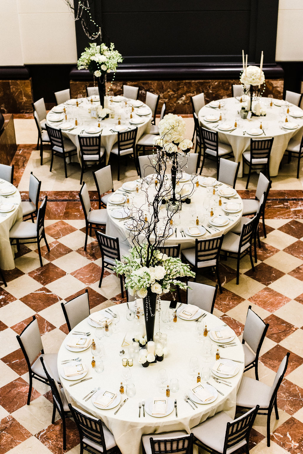 Great Gatsby themed wedding for Tyler & Melanie Anderson at the Goodwin hotel in Hartford, CT. Black chairs, tall centerpieces by Ruth L.  - Pearl Weddings & Event