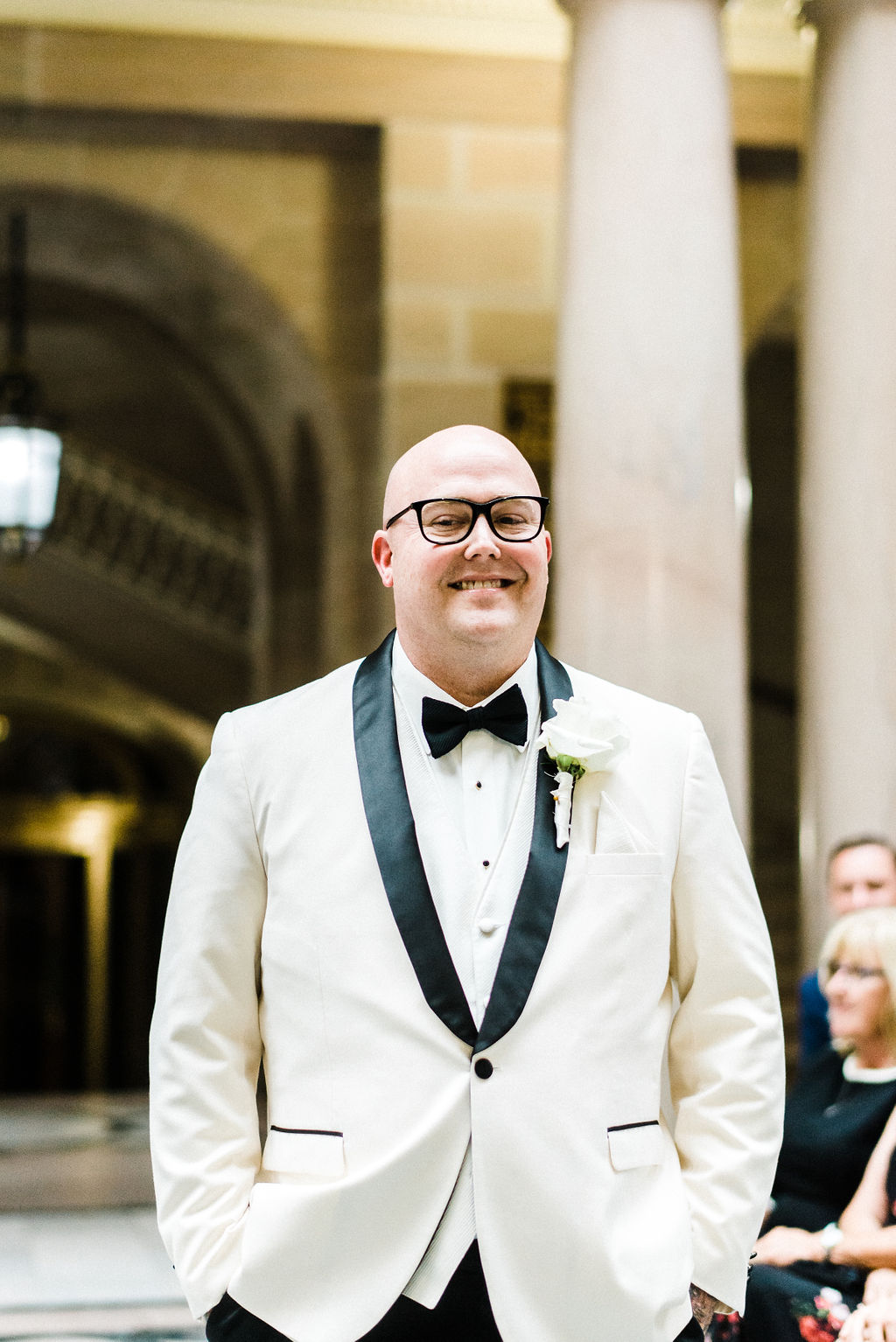 The groom waiting for his bride to walk down the aisle. He is wearing a white vera wang suit with black bow tie. - Pearl Weddings & Events