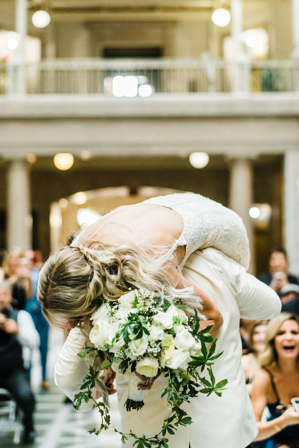 Groom carries bride over his shoulder down the aisle at their Great Gatsby themed wedding - Pearl Weddings & Events