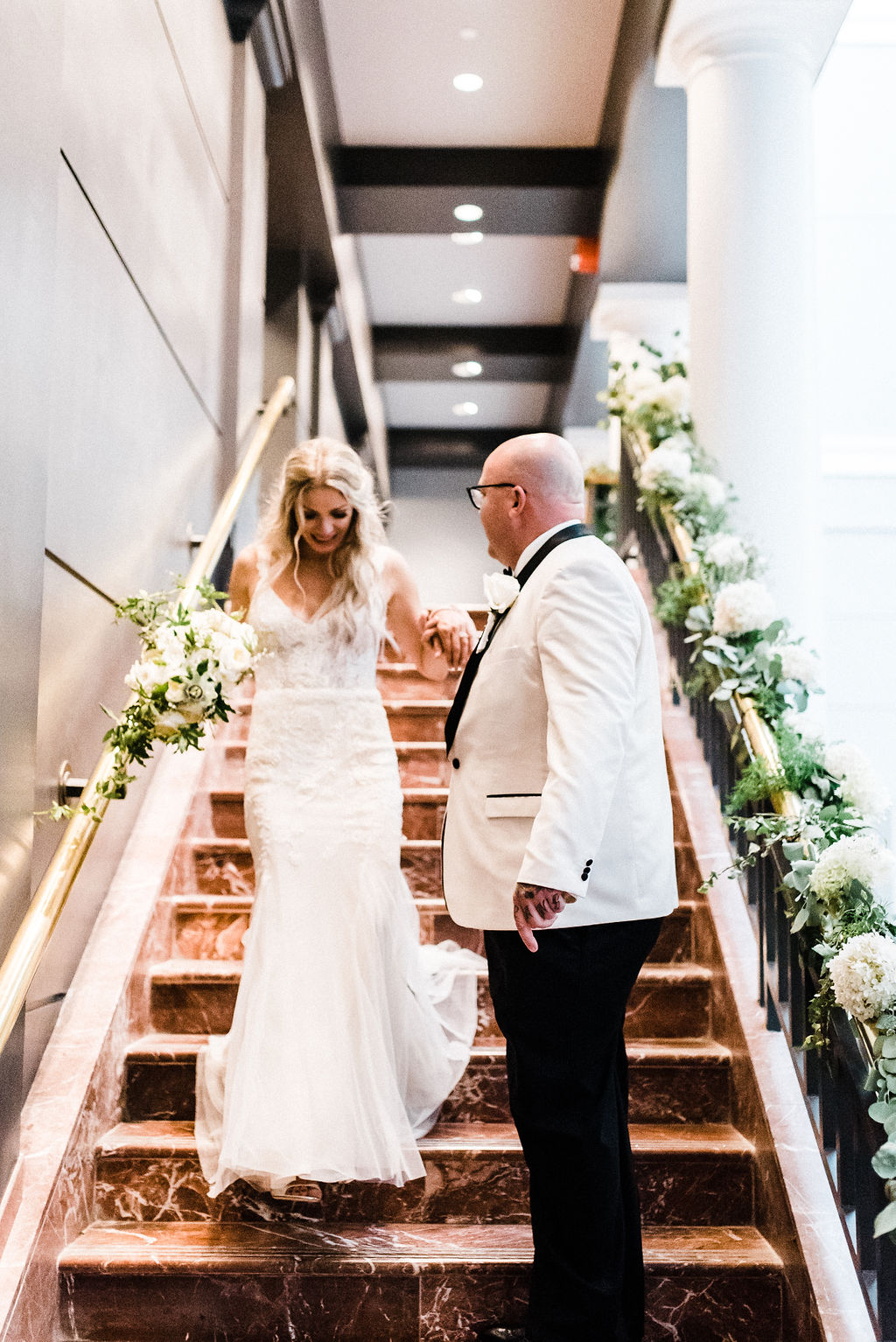 Groom assists his bride down the staircase surrounded by lush greenery into the ballroom - Pearl Weddings & Events