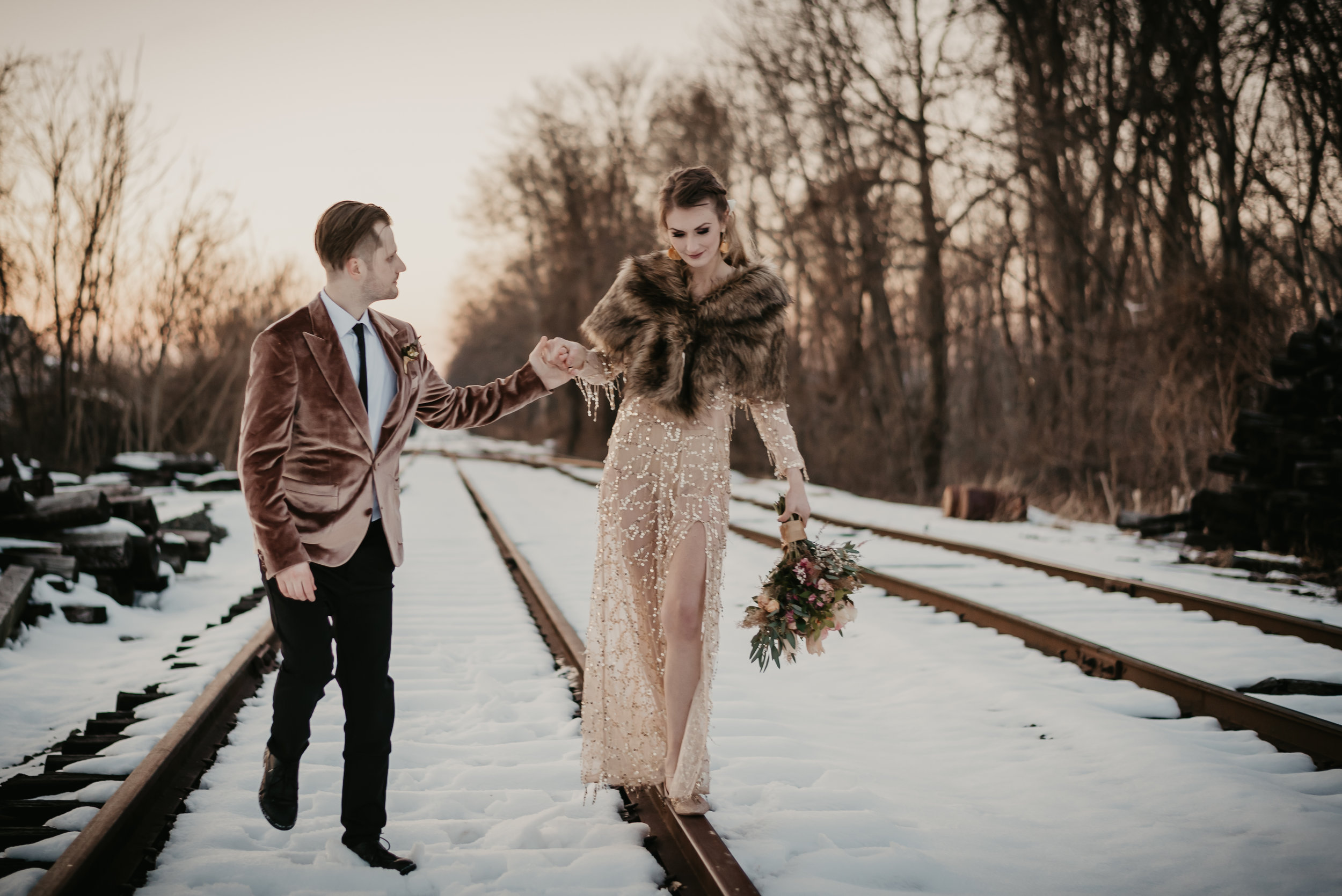 Groom in a velvet jacket, bride in a sequins dress with a shawl on her wedding day walking the train rails in the middle of winter! - Pearl Weddings & Events