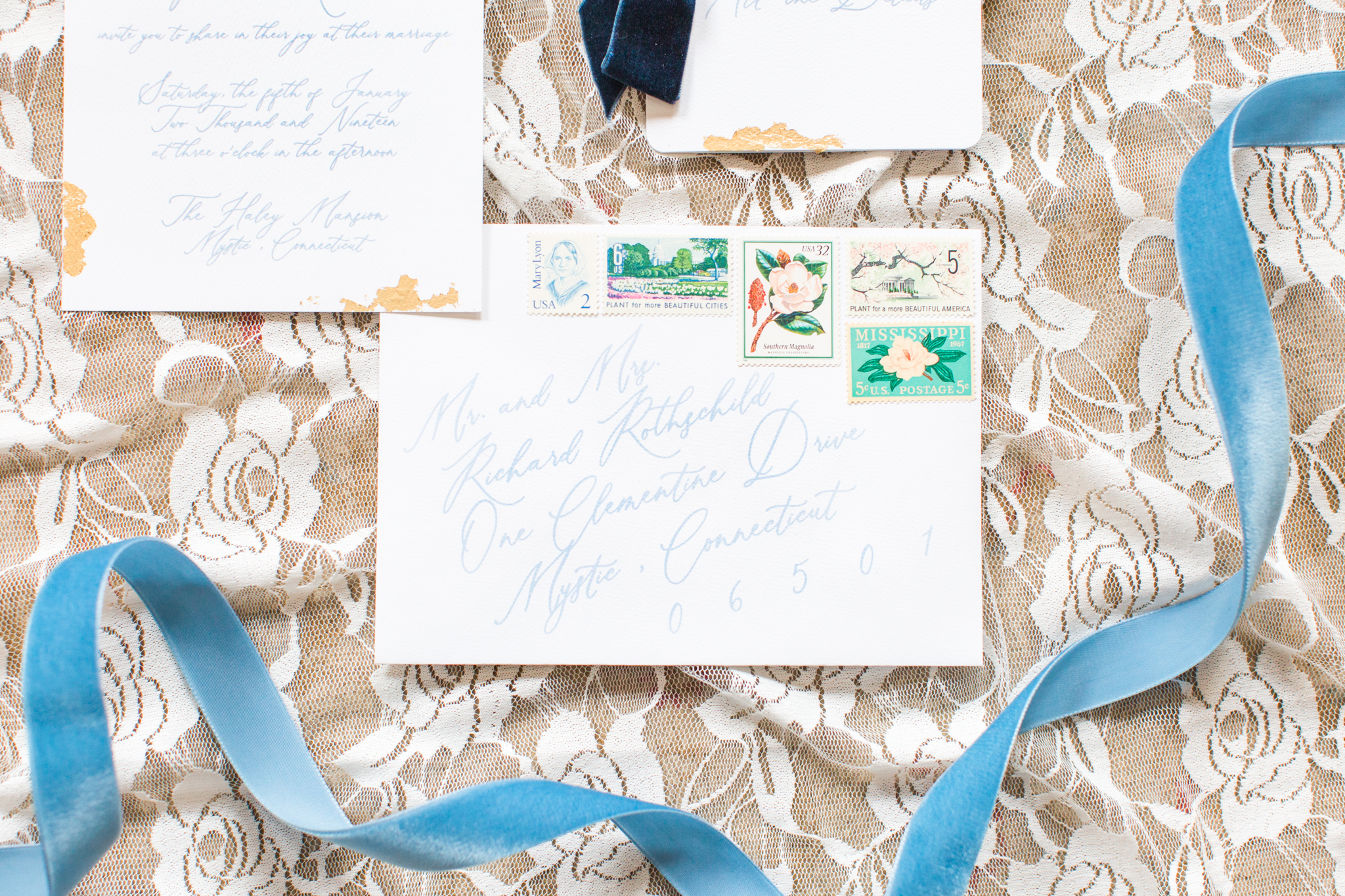 Invitation suite flat lays showcasing the vintage stamps, light blue fonts, gold leaf design for this elegant wedding - Pearl Weddings & Events