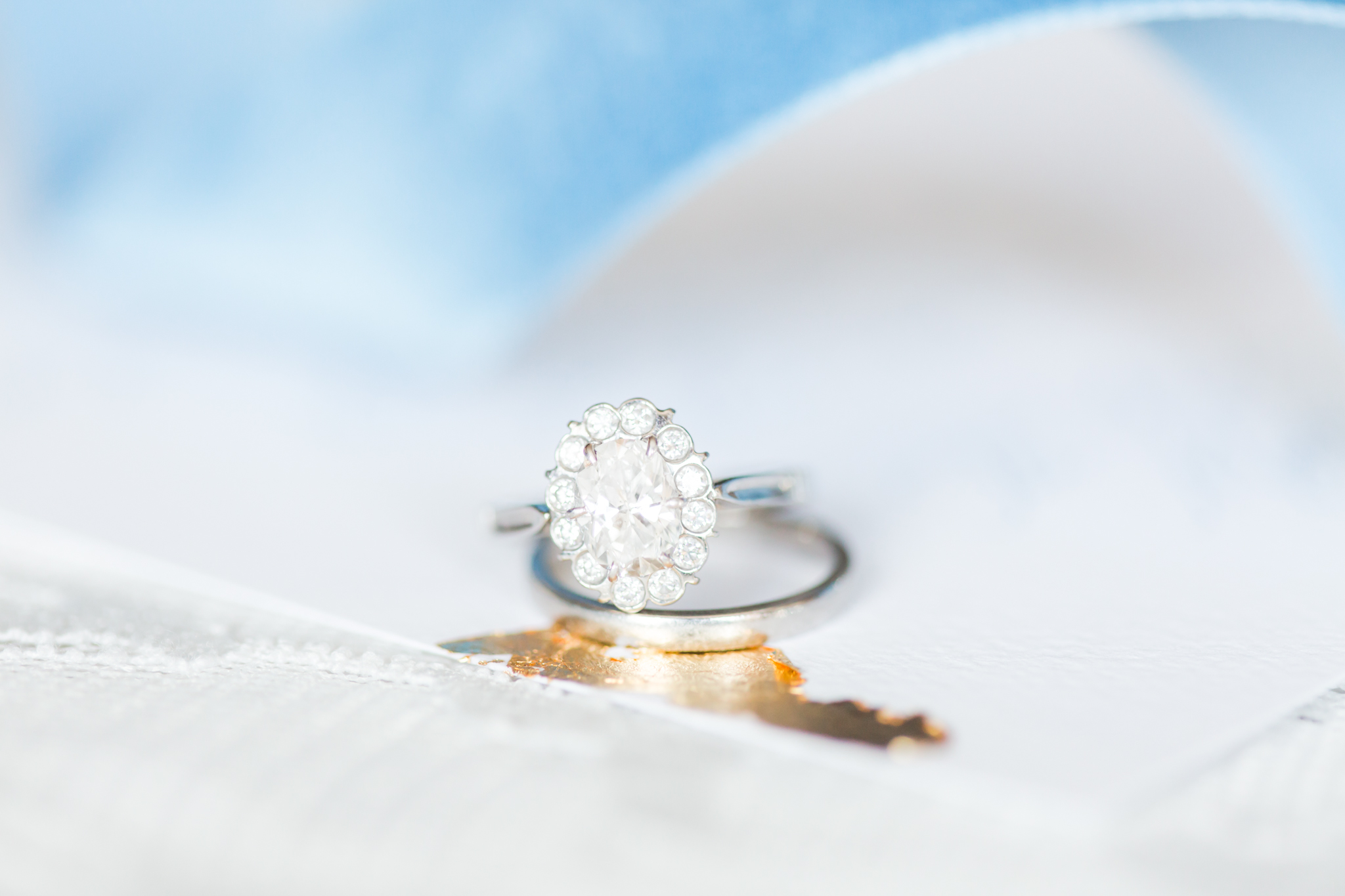 Oval platinum engagement ring with a halo and a plan platinum band - Pearl Weddings & Events