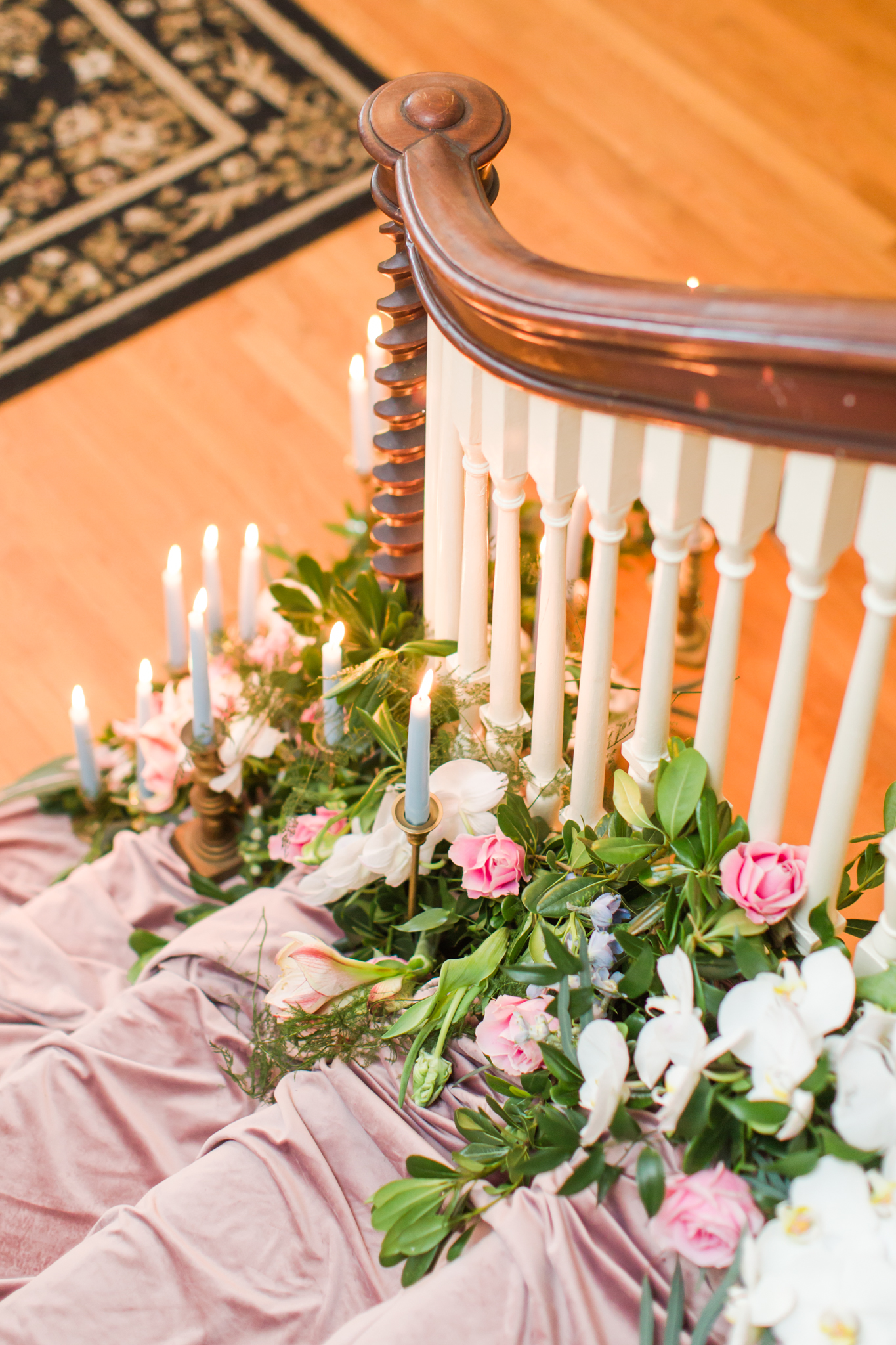 Pink velvet covered staircase with white orchids, pink florals, greenery and light blue candles in gold holders - Pearl Weddings & Events