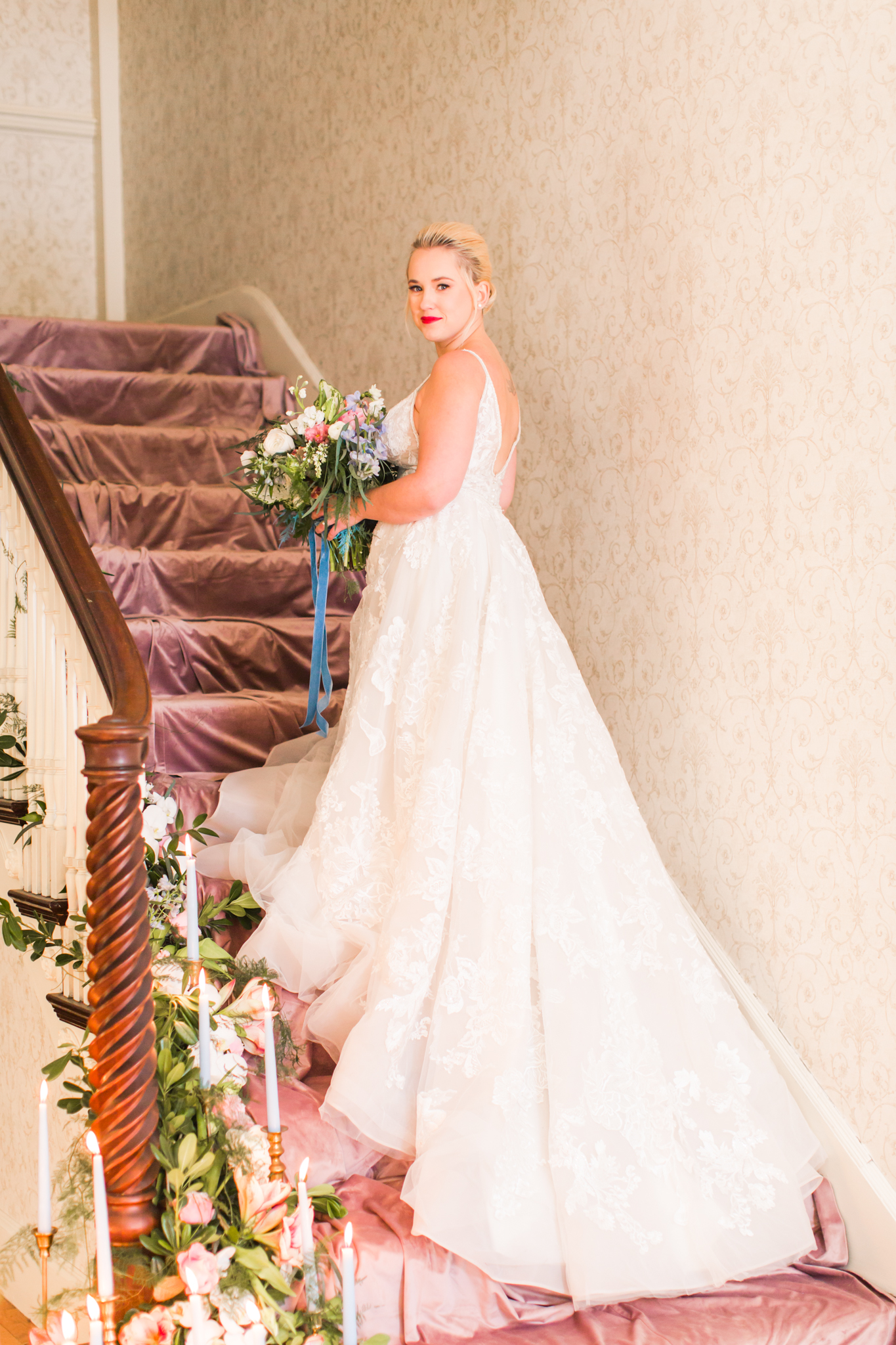 Bride posed on the staircase with pink velvet stairs and florals cascading down with light blue candles - Pearl Weddings & Events