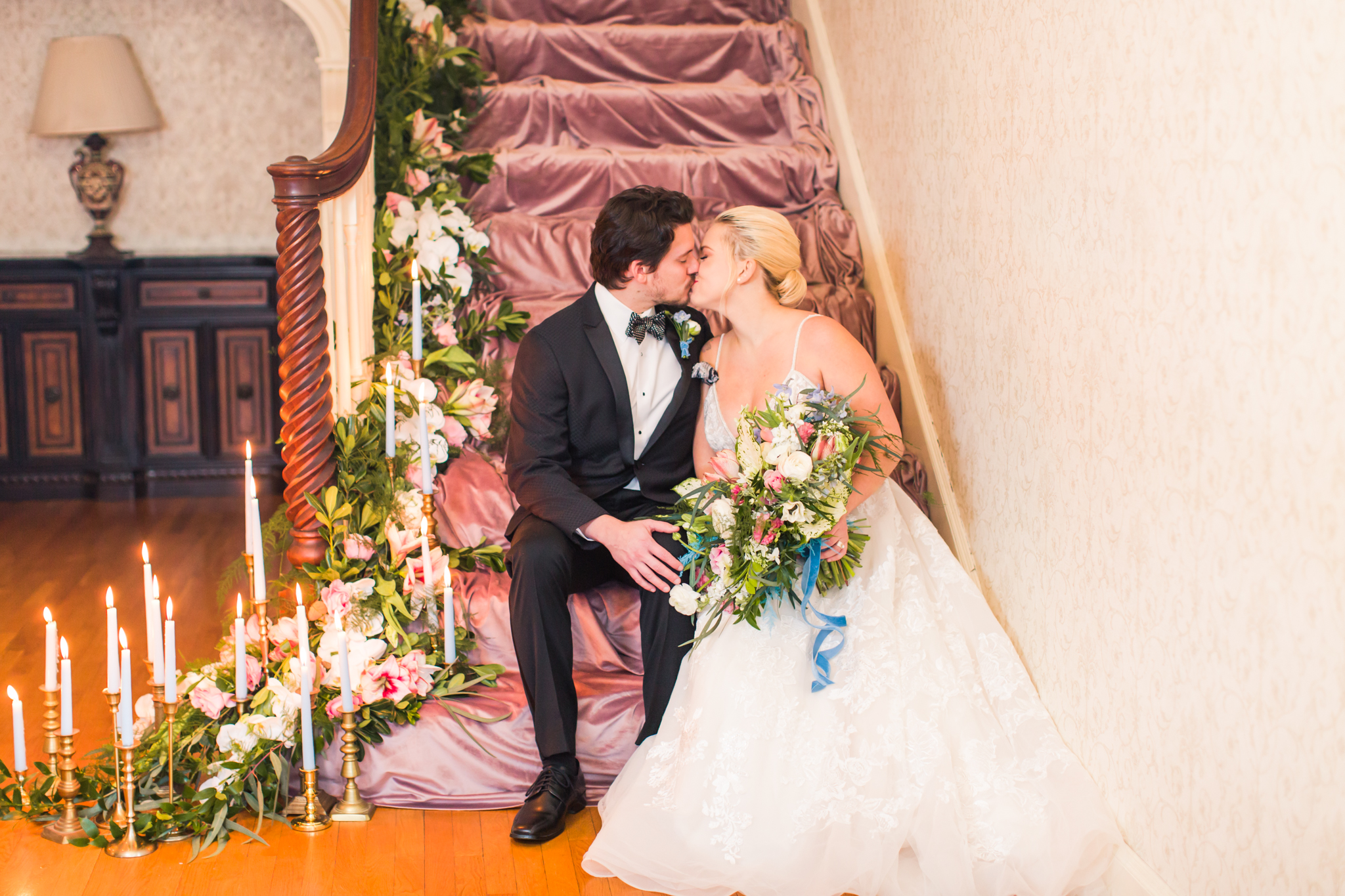 First kiss and first look one a pink velvet covered stair case covered in florals and candles - Pearl Weddings & Events
