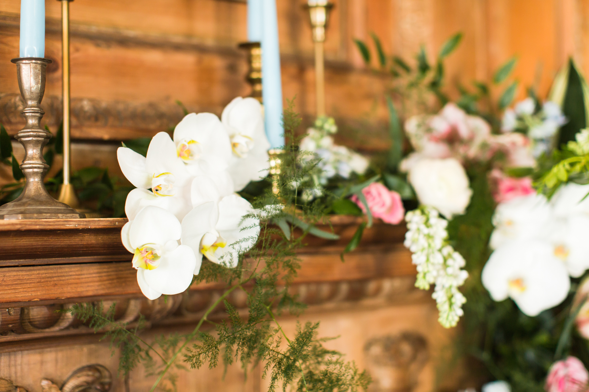 White orchids, greenery, pink and coral florals with light blue candles and gold candle holders on a wooden fire place - Pearl Weddings & Events