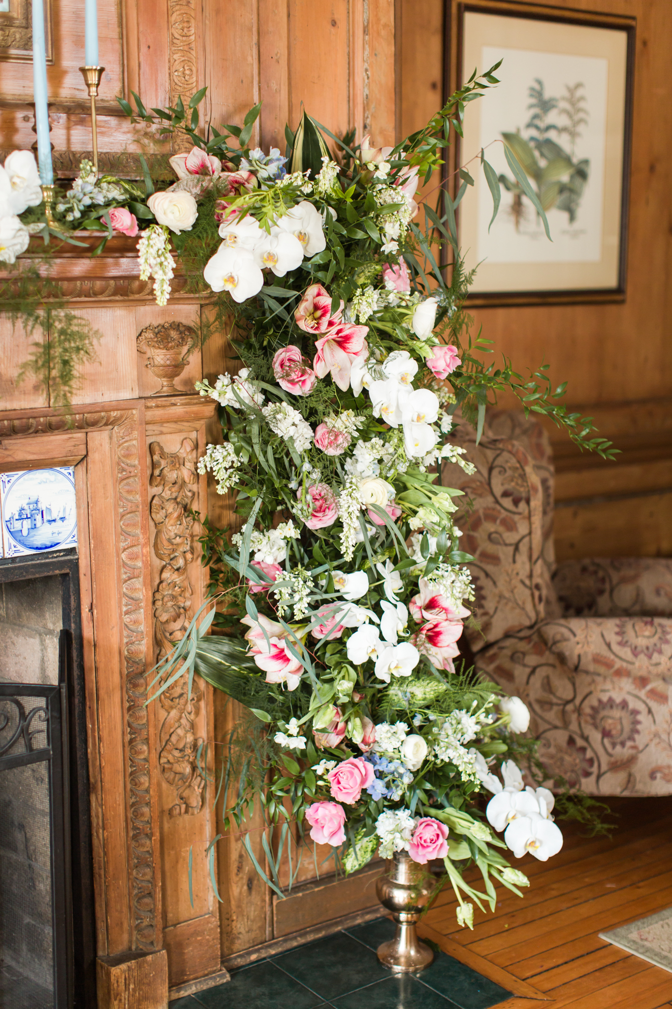 Lush greens, pinks and white orchids arching up a candle light fire place for an intimate ceremony at the Haley Mansion in Mystic Connecticut - Pearl Weddings & Events